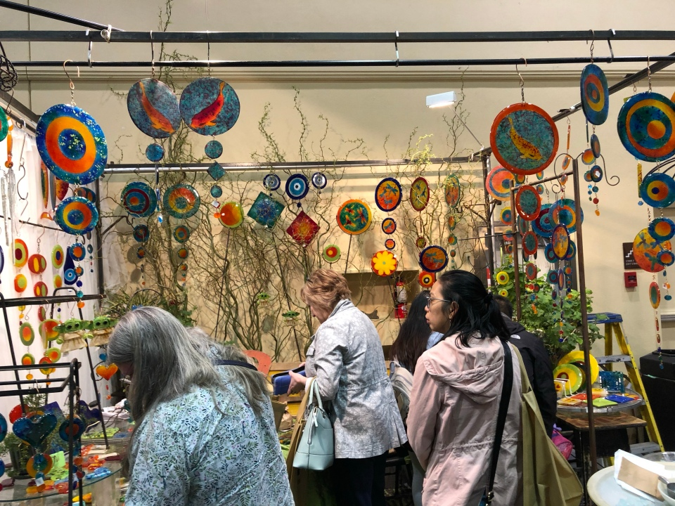 People shopping in an art booth