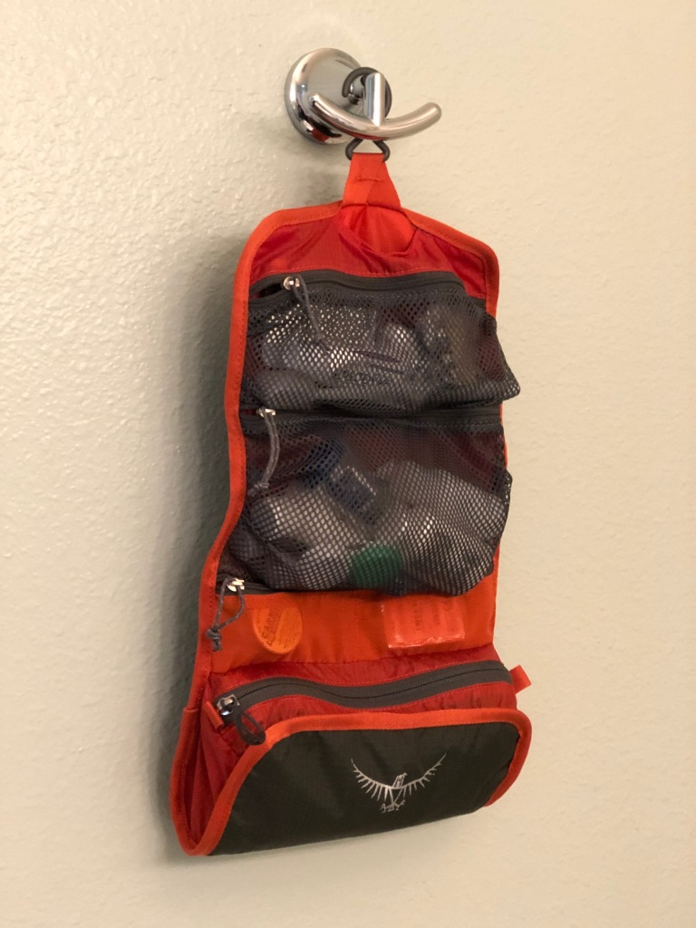 Osprey toiletry bag hanging on a hook.