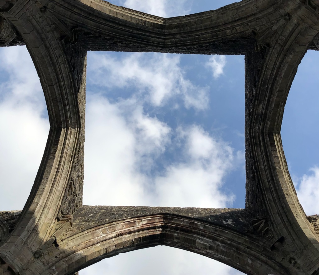 Tintern Abby view through destroyed roof to blue sky and puffy clouds.
